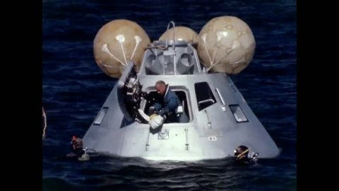 CIRCA 1969 - After Apollo 11's water landing, Buzz Aldrin inflates a raft while rescue divers tread water nearby.