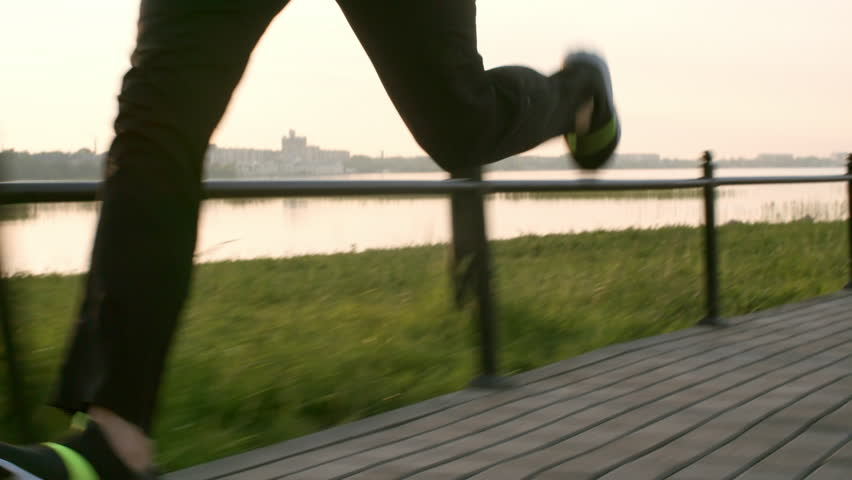 Tilt up of athletic male runner jogging outdoors along riverside promenade while working out in the morning | Shutterstock HD Video #1016285206