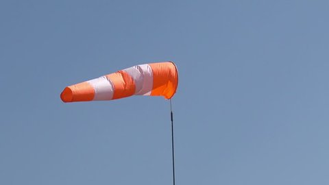 The aerodrome white-red cone-wind indicator flutters against the blue sky on a sunny day