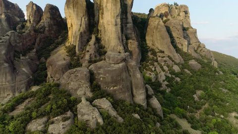 Aerial shot taking off over Meteora natural mountains amazing landscape at sunset raising up helicopter rock formation in central Greece Kalambaka