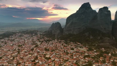 Aerial shot magnificent mountains Meteora flying over great landscape city Kalampaka in natural valley at amazing sunset evening colored sky bird in front of moving camera