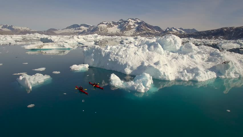 Greenland, aerials from kayaker paddling beneath icebergs