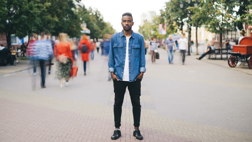 Time-lapse portrait of depressed African American man looking at camera standing alone in the street, hands in pockets, while people are rushing around him. | Shutterstock HD Video #1016312956