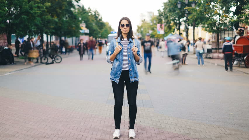 Time-lapse of attractive young woman wearing sunglasses standing alone in big city with backpack and looking at camera when crowds of people are passing by.