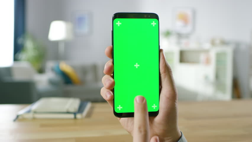 Close-up of a Man Holding Green Mock-up Screen Smartphone and Using Touchscreen Gestures. Touching Mobile Phone Chroma Key Screen. In the Background Cozy Homely Atmosphere. Shot on RED EPIC-W 8K.