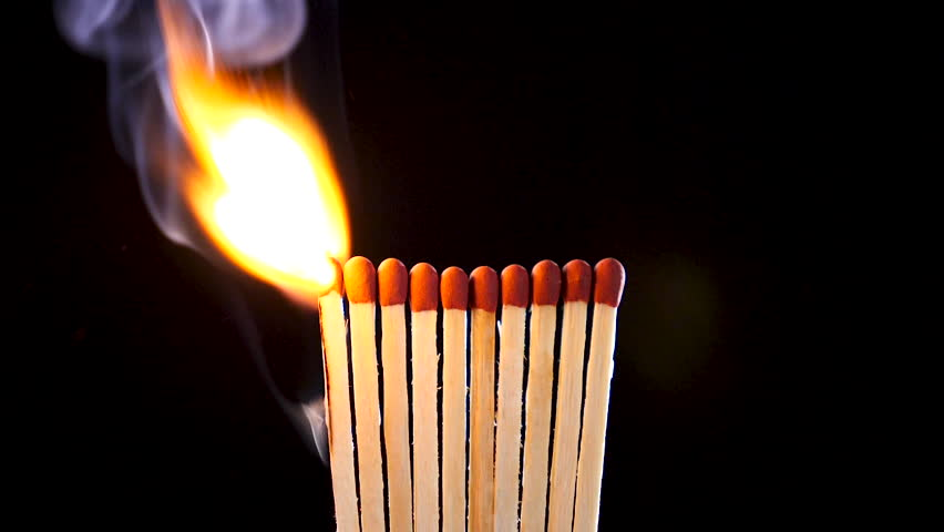 Matches light up one by another in series on black background. Slow motion footage