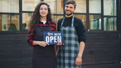 Slow motion portrait of beautiful lady and her business partner handsome man holding open sign informing customers about opening of their cafe and welcoming people.