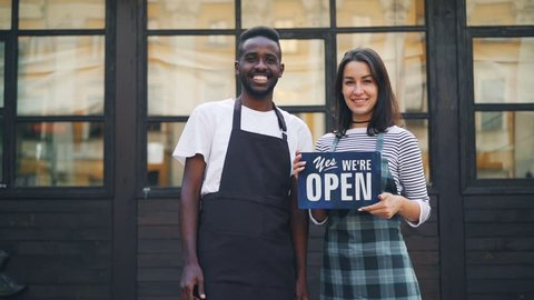Slow motion portrait of man and woman business partners holding cafe open sign and smiling looking at camera. Starting business and success concept.