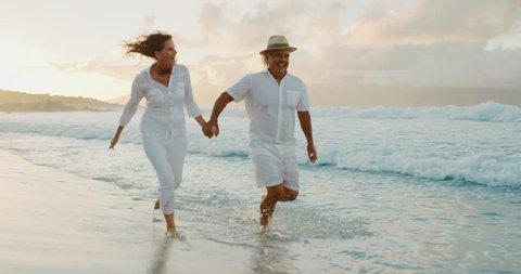 Romantic middle age retired couple enjoying sunset walk on vacation