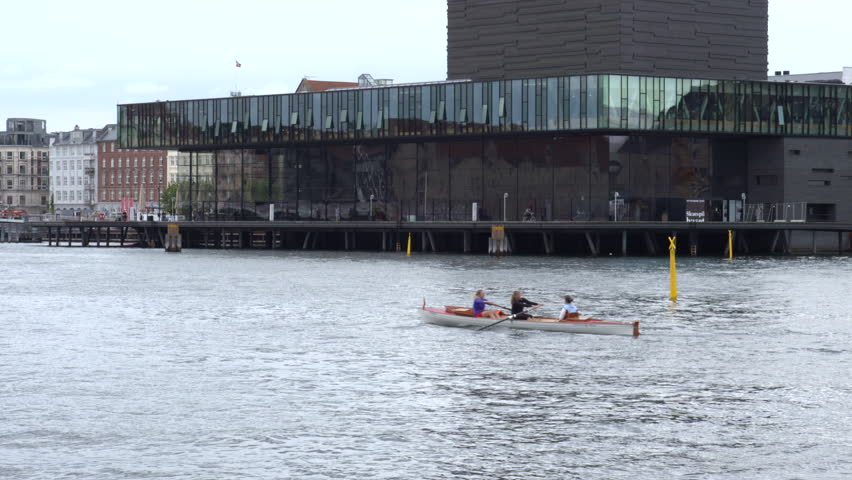 Copenhagen, Denmark - 21 September 2015: A kayak makes it way past The Royal Danish Playhouse at the harbor front