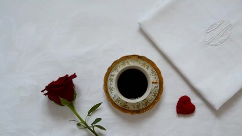 cup coffee, romantic moment, hand taking cup of coffee on decorated tablecloth background,  red roses with heart , top view