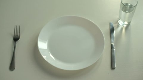 Hands tied with measuring tape lying on plate, obsession with diet, calories