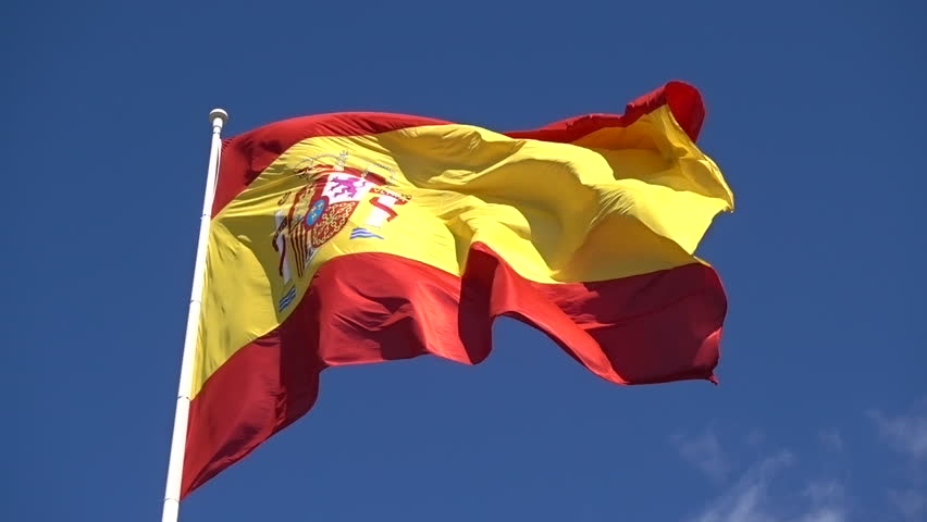 Close-up of Spain flag in front blue sky slow waving on wind