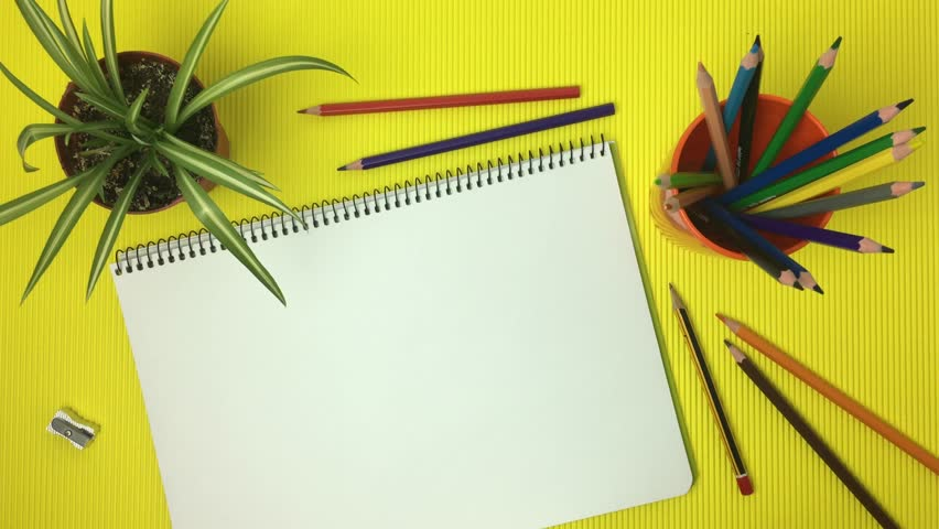 Table scene with notebook, coloured pencils, on yellow background. | Shutterstock HD Video #1016464906