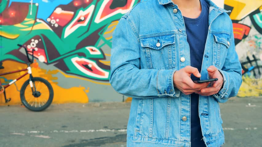 Teenager in a jeans jacket is standing with his mobile phone near a graffiti wall | Shutterstock HD Video #1016466586