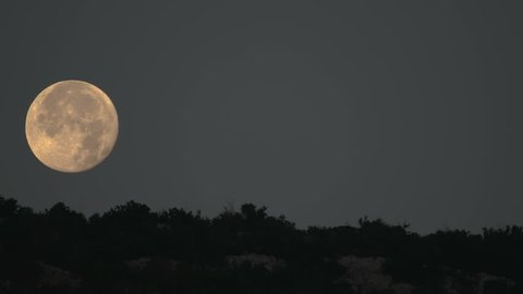 Time Lapse of beautiful and yellow Moon goes down behind a landscape