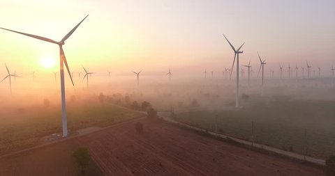 Aerial view of Wind turbines Energy Production- 4k aerial shot on sunrise. 4k drone footage turbines at sunrise with clouds. Sustainable development, environment friendly, renewable energy concept.