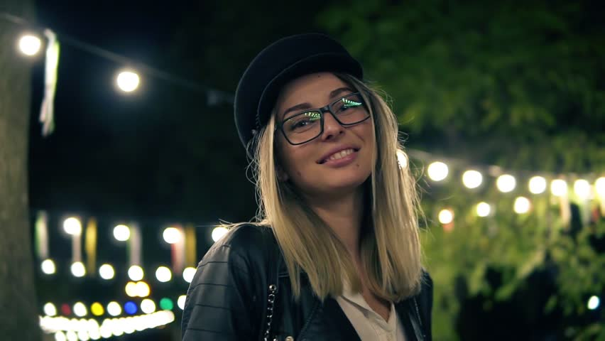 Portrait of a beautiful girl in stylish hat, fashion glasses and a black leather jacket walks in the night park. Light of a cafe lamps on the background. Blonde girl smiling, posing for camera