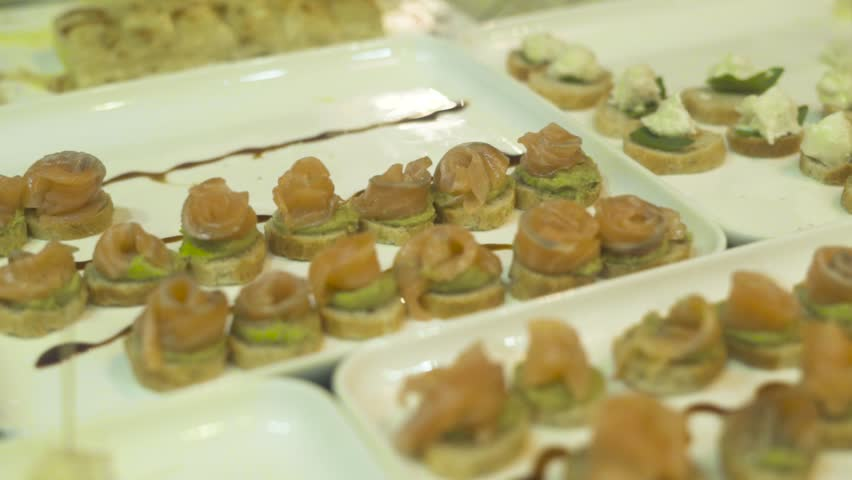 Delicious snacks and canape on table at event party. Close up appetizing snacks on party table at holiday evening