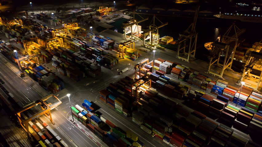Aerial hyperlapse - Night shot of busy industrial port. Footage of seamless transport routes supply chain