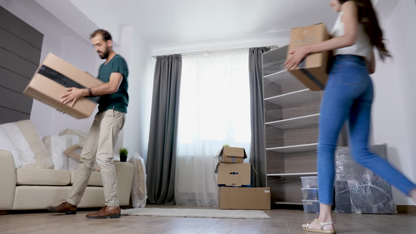 Young couple moving cardboard boxes in their new house. Happy family | Shutterstock HD Video #1016554396