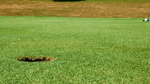 Close up shot of golf putt on beautiful golf course - ball barely misses hole in green