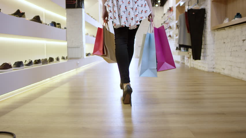 Beautiful fashion female is walking through a department store in colorful garments. Close-up shot of legs | Shutterstock HD Video #1016620846