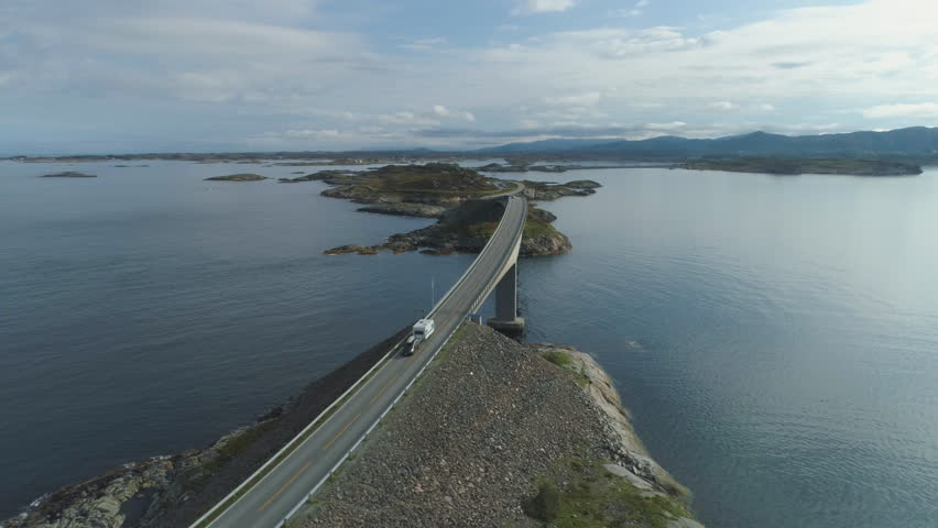 Car with Motorhome travels on Storseisundet Bridge. Atlantic Ocean Road in Norway. Aerial View. Drone Orbits Around
