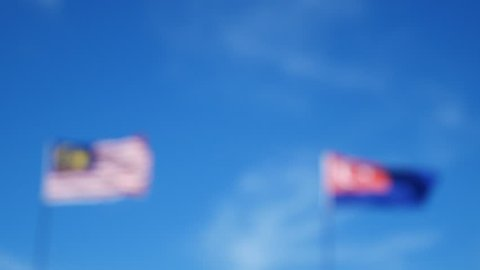 A motion of Malaysia and Johor Flag fluttering with blue sky and moving clouds. Patriotic concept