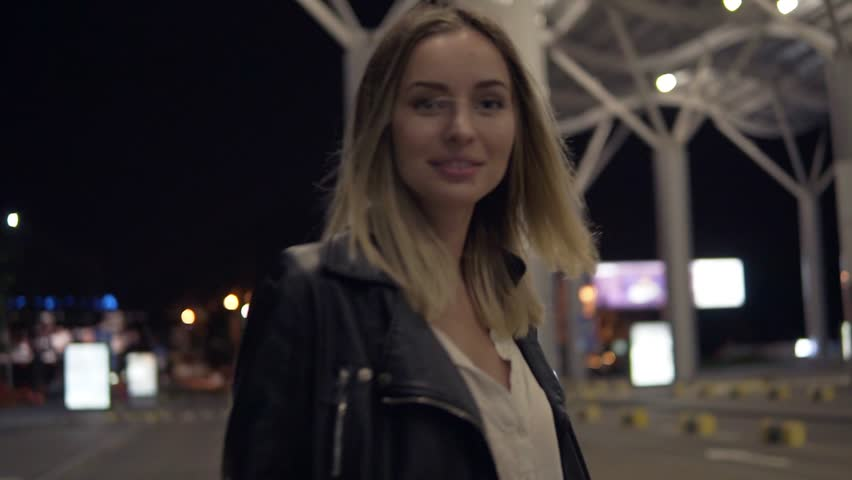 Young blonde woman in jeans and black leather jacket jumping on yellow street bumpers at night, having fun. Street, white city light, crosswalk on the background. Posing for camera, rare view