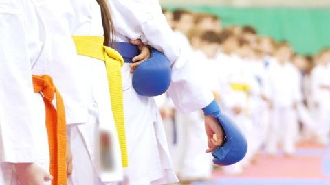 Hands of children standing in a row of karatekas in gloves