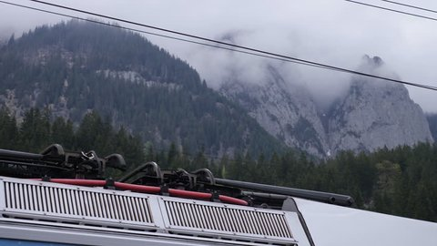 Train Pantograph is going up and down with mountains in the background 4k