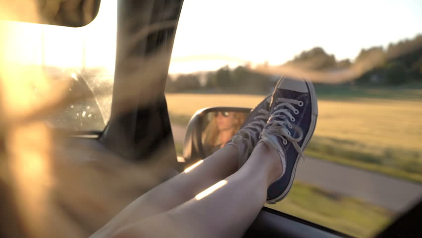 A young redhead woman enjoys traveling in a car by sticking out her legs in an open window. Slow motion. | Shutterstock HD Video #1016690836