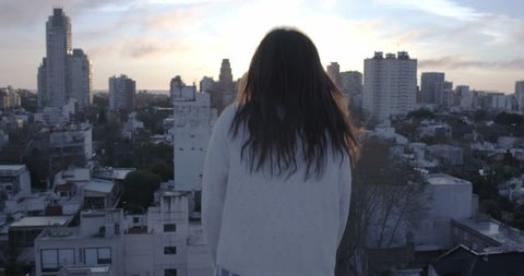 Beautiful woman on a rooftop opening her arms into the golden sunrise and looking to camera– 4K