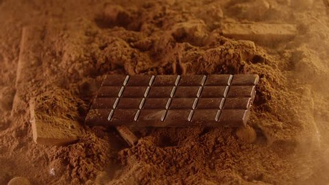 Chocolate bar falling into cacao powder . Spices. Shot on Red Dragon Cinema Camera in slow motion 200 fps .