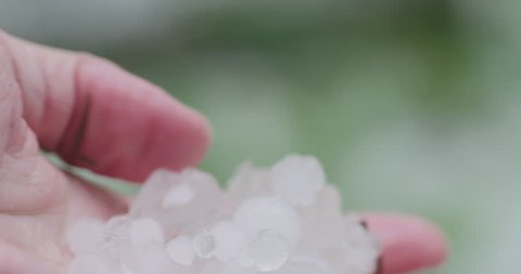 Slow motion closeup pov male hand holding hailstones after hailstorm