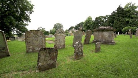 Gravestones in English churchyard DOLLY SHOT
