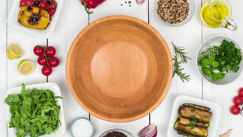 Top view on fresh salad with grilled vegetables in wooden bowl with food ingredients on white rustic table. 4k stop motion animation. | Shutterstock HD Video #1016789056
