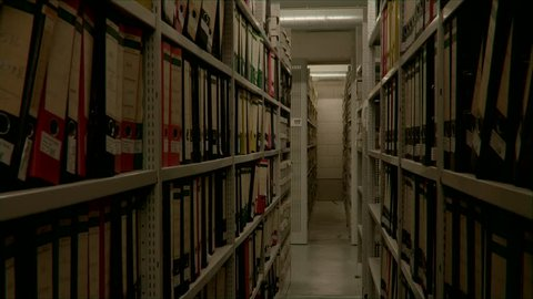 Slow camera movement between two archive shelves filled with folders. The image can be used for the integration of archive texts in films and reports. Thanks to the 50 frames it can be slowed down.