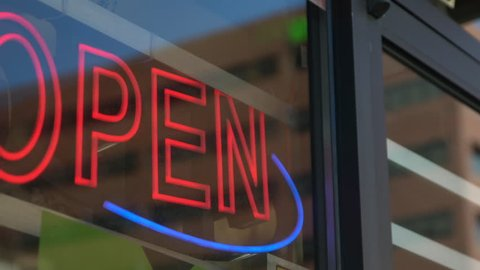 Panning shot of a blinking neon open sign indicating a store or place of business is open.
