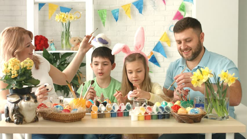 Happy family with two children in bunny's ears fools around during Easter eggs decoration | Shutterstock HD Video #1016797876