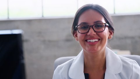 Young female doctor in glasses smiling to camera, close up