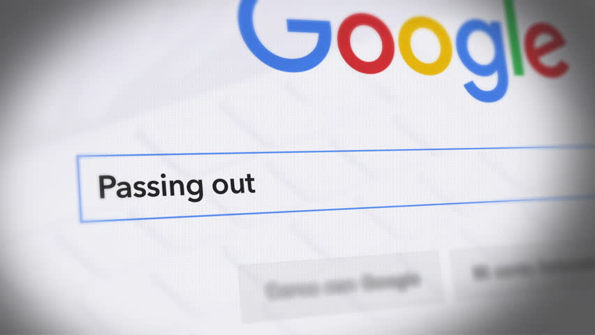 USA-Popular searches in 2018 Google Search Engine - Search For passing out -  Monitor with reflection hands typing a search on google