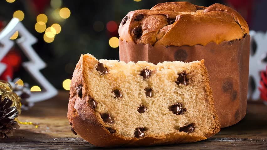 Delicious Panettone slice with candied fruits with blinking blurred christmas lights. Chocotone