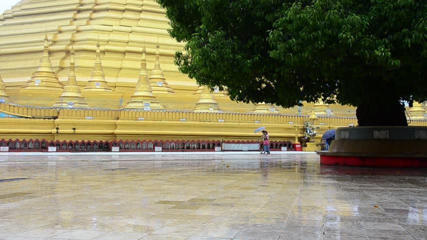 People hold umbrella walking around Shwemawdaw Paya Pagoda at raining time in Bago, Myanmar