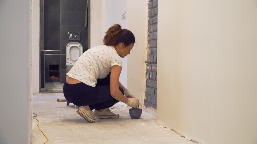 Squatting girl paints brick wall in gray using brush. Renovation in the corridor of empty apartment with white walls. Bathroom in the background.   Shutterstock HD Video #1016876536