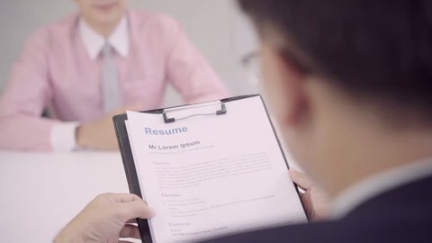 Slow motion - Attractive young Asian businessman in a job interview with corporate personnel manager who reading his CV. Asia businessman talking to male candidate at desk, interviewing job applicant.