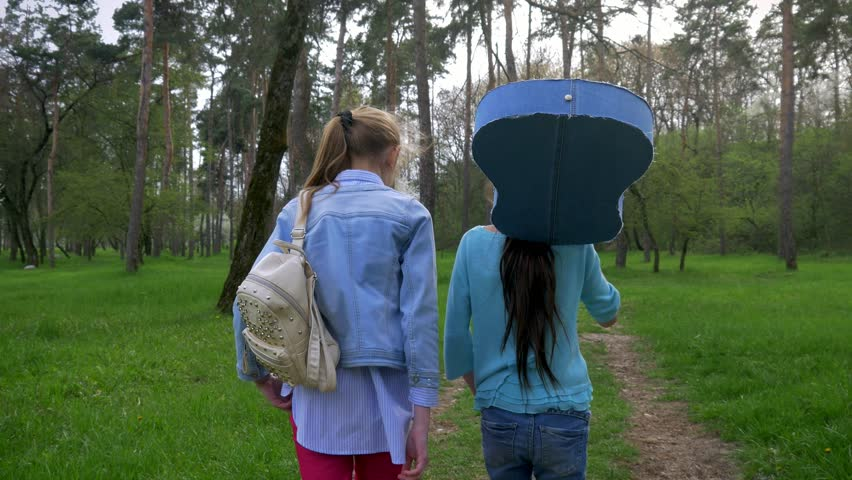 Two little girlfriend walk in the Park with acoustic guitar on shoulder. concept emotions and joy #1016884336