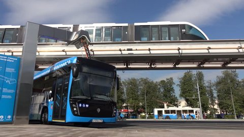 Moscow, Russia-September 2017:The concept of urban transport .Blue electric bus at the charging station.Modern train passing on the monorail. The concept of ecological future.