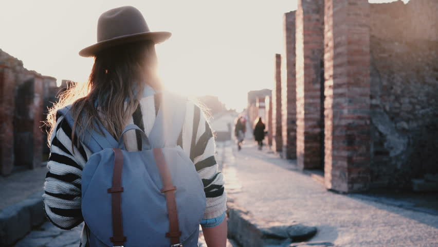 Camera follows successful female travel blogger in hat with backpack walking along ancient street in Pompeii on sunset. #1016897836